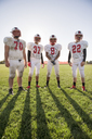Portrait of American football players standing on field during sunny day - CAVF14011
