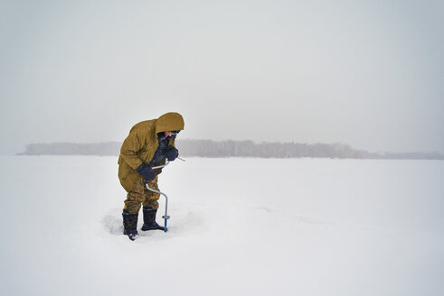 Senior man drilling in frozen lake against clear sky - CAVF14044