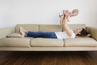 Happy mother lifting daughter while lying on sofa at home - CAVF14314