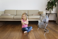 Happy girl sitting by electric fan on hardwood floor at home - CAVF14320