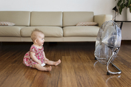 Happy baby girl sitting in front of electric fan on hardwood floor at home - CAVF14323