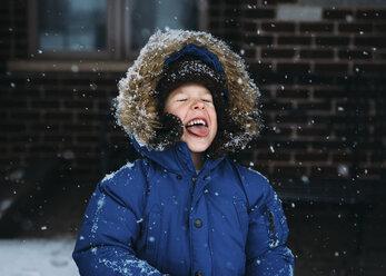 Cheerful boy enjoying snowfall - CAVF14497