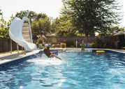Boy looking at brother jumping in swimming pool on sunny day - CAVF14503