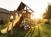 Boy playing with jungle gym in backyard during sunset - CAVF14509