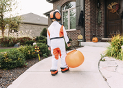 Rear view of boy in Halloween costume with container walking in yard - CAVF14551