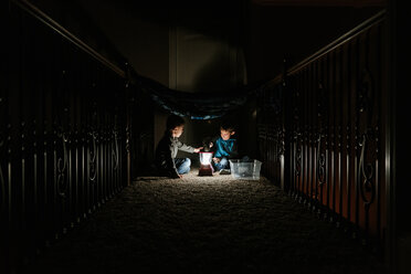 Brothers playing with lantern in darkroom at home - CAVF14554