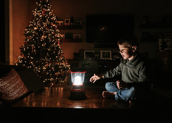 Boy with lantern sitting on table by Christmas tree at home - CAVF14560