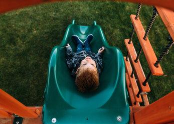 High angle view of happy boy sliding at park - CAVF14563