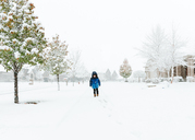 Boy walking snow covered road during foggy weather - CAVF14566