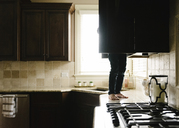 Low section of boy searching something in cabinet while standing on kitchen counter at home - CAVF14593