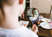 Reflection of boy painting face in mirror - CAVF14596
