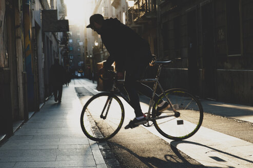 Side view of man riding bicycle on footpath during sunset - CAVF14683