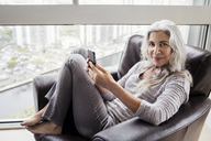 Portrait of smiling mature woman holding smart phone while sitting on armchair at home - CAVF14791