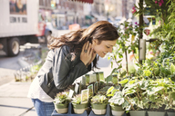Happy woman smelling plants at market stall - CAVF14806