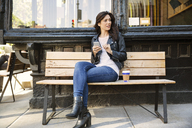 Thoughtful woman holding smart phone while sitting on bench at sidewalk cafe - CAVF14809