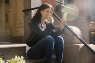 Happy woman using smart phone while sitting on steps - CAVF14812
