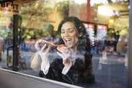 Happy woman eating pizza in restaurant - CAVF14824