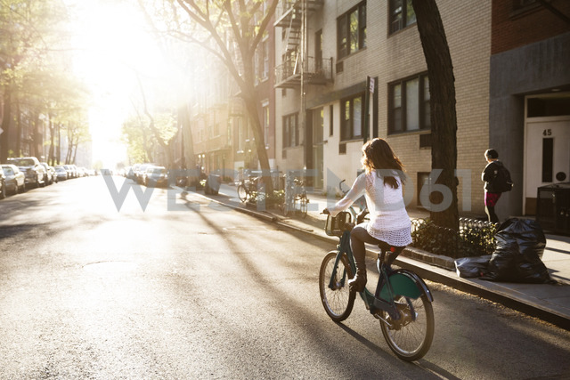 Rear view of young woman riding bicycle on street - CAVF14827