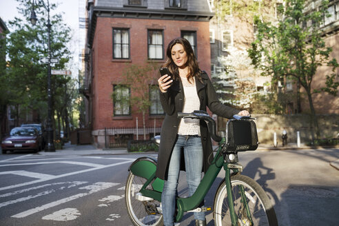Young woman using smart phone while standing with bicycle on street - CAVF14830