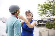 Mature woman assisting man in wearing bicycle helmet against clear sky - CAVF15055