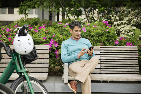 Mature man using smart phone while sitting on bench in park - CAVF15058