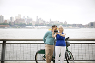 Cheerful mature couple taking selfie on promenade by river in city - CAVF15061