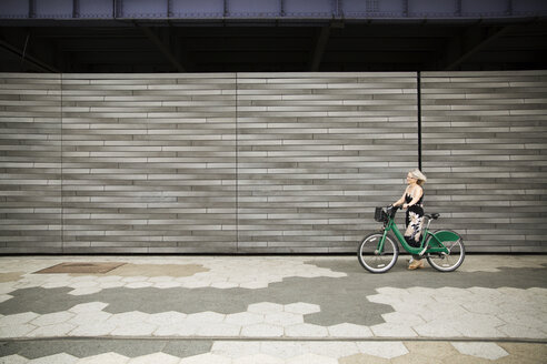 Side view of mature woman walking with bicycle on footpath by wall - CAVF15064