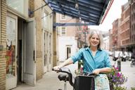Portrait of happy mature woman standing with bicycle on sidewalk - CAVF15067
