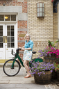 Portrait of happy mature woman standing with bicycle on sidewalk outside building - CAVF15070