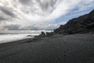 Scenic view of black sand beach against cloudy sky - CAVF15166
