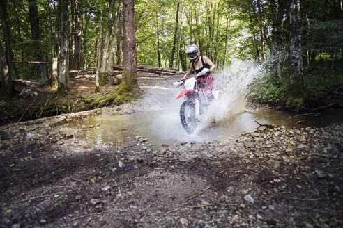 Young female biker riding dirt bike on puddle in forest - CAVF15235