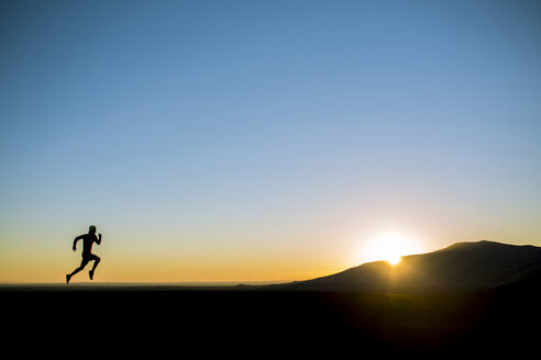 Silhouette man running on field against clear blue sky - CAVF15244