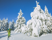 Full length of man skiing on snow covered field against clear blue sky - CAVF15262