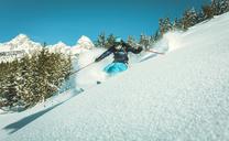 Woman skiing on ski slope against blue sky - CAVF15274