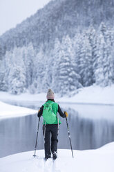 Rear view of female hiker standing at snow covered lakeshore - CAVF15283