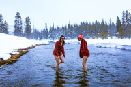 Female friends enjoying in lake against sky during winter - CAVF15289