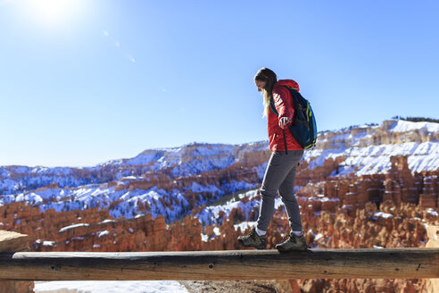 Female hiker walking on wood at Bryce Canyon National Park against clear blue sky - CAVF15331