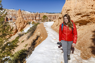 Portrait of hiker walking on snow covered mountain at Bryce Canyon National Park - CAVF15334