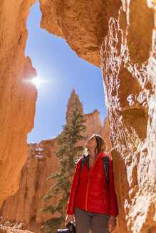 Low angle view of hiker looking up while standing by rock formations during sunny day - CAVF15337