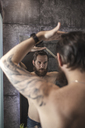 Portrait of bearded man looking at his mirror image while combing his hair - VPIF00387