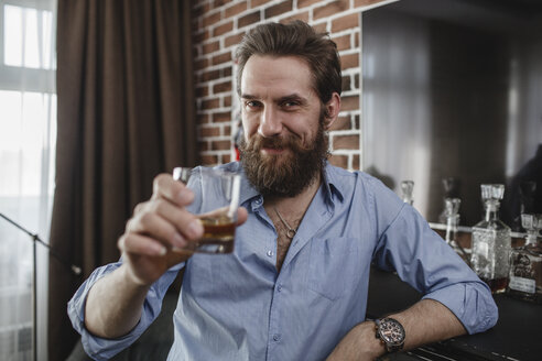 Portrait of smiling man with glass of whiskey at home - VPIF00393