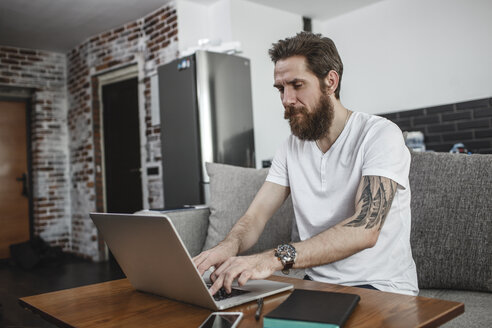 Bearded man sitting on the couch at home using laptop - VPIF00396