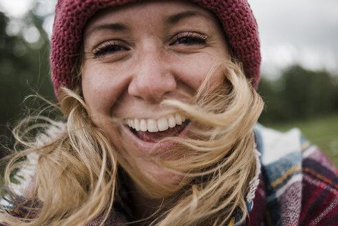 Portrait of cheerful woman wearing knit hat - CAVF15354