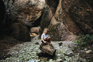 Girl looking away while crouching on log against rock formation - CAVF15381