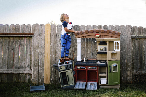Cheerful girl standing on toy kitchen in backyard against clear sky - CAVF15405