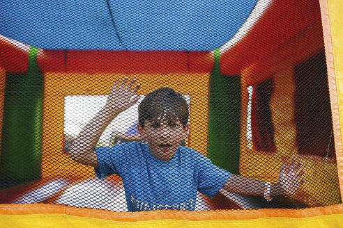 Portrait of boy standing in trampoline - CAVF15411