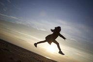 Happy girl jumping at beach against sky during sunset - CAVF15519