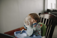 Baby boy eating food while sitting on high chair at home - CAVF15567