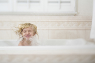 Girl with eyes closed splashing water while bathing in bathtub at home - CAVF15609