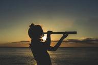 Silhouette girl using telescope against sea during sunset - CAVF15618